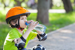 The boy  in a safety helmet drinks water Royalty Free Stock Photo