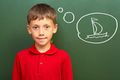 Boy and sail. Portrait of smart lad by the blackboard thinking of sail and looking at camera Stock Images