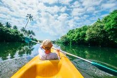 Boy sailing in canoe on tropical lagoon stock image