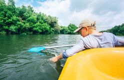 Boy sailing in canoe on tropical lagoon - active leisure time Royalty Free Stock Image