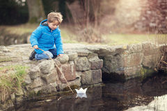 Boy sailing a paper boat. Child playing with paper boat and stick on bridge by water royalty free stock image