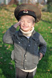 Boy salutes in military cap Royalty Free Stock Image