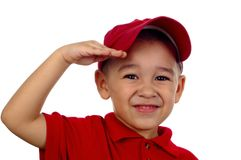 Boy Saluting. Portrait of a young boy with a red hat and shirt saluting and smiling stock photo