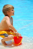 Boy with sand bucket. A view of a young boy playing in shallow water with a sand bucket or pail and small sand shovel royalty free stock photos