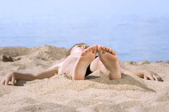 Boy in sand on seashore Stock Photos