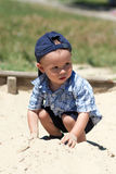 The boy in a sandbox. The boy in a dark blue baseball cap sits in a sandbox Royalty Free Stock Photo