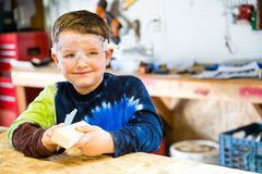 Boy sanding wooden block in workshop. As he builds car for Pinewood Derby Royalty Free Stock Photo