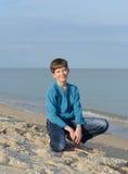 Boy on a sandy beach. Early evening. Teenager on the beach Royalty Free Stock Photos