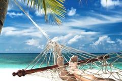 Boy with sandy feet lying in a hammock Stock Photo