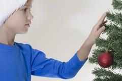 Boy in Santa cap near Christmas tree Stock Photography