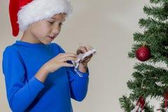 Boy in Santa cap near Christmas tree with xmas toy Royalty Free Stock Image