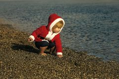 Boy in santa claus costume playing with pebbles on beach stock photos