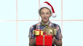 Boy in Santa Claus hat with gift boxes. stock footage