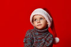 boy in Santa Claus hat portrait dreams of gifts on a red background stock images