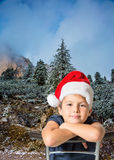 Boy in Santa Claus hat smiling on pine forest Royalty Free Stock Photo