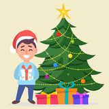 Boy in Santa Claus hat standing near decorated Christmas tree wi. Merry Christmas and a Happy New Year greeting card. Boy in Santa Claus hat standing near Stock Image