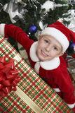 Boy In Santa Claus Outfit Holding Christmas Present Royalty Free Stock Photo