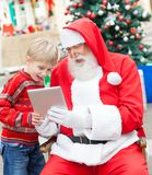 Boy And Santa Claus Using Digital Tablet Stock Images