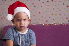 Angry boy in a santa hat Royalty Free Stock Photos