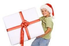Boy with santa hat and big present. Happy boy with christmas hat and big present - isolated Royalty Free Stock Photo