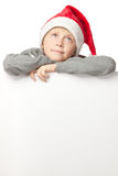 Boy in Santa hat with blank board Royalty Free Stock Image