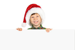 Boy in Santa hat with blank board. Happy little boy in Santa hat with blank board isolated on white background Royalty Free Stock Photos