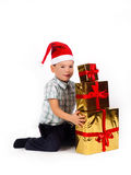 Boy in Santa hat with a bunch of gifts Stock Images