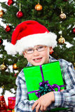 Boy with santa hat with christmas gift smiling Stock Photos