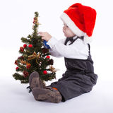 Boy with santa hat decorate christmas tree Stock Photo