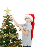Boy with santa hat decorates the Christmas tree Stock Photos