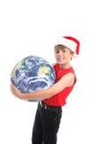 Boy in Santa hat with globe. Cute boy in Santa hat holding large World globe; isolated on white background Stock Image