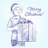 Boy in Santa hat holding  Christmas present hand Royalty Free Stock Photo