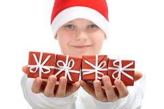 Boy in Santa hat holds Christmas presents isolated Royalty Free Stock Photos