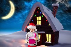 Boy in santa hat looking at christmas gift. Against digitally generated background royalty free illustration