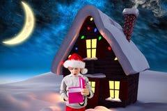 Boy in santa hat looking at christmas gift Stock Image