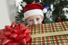 Boy In Santa Hat Peeking Over Gift Box. Portrait of a cute elementary boy in Santa hat peeking over gift box royalty free stock photography