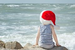 Boy in Santa hat sitting on the beach. Back view Stock Image