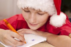Boy in santa hat writing Royalty Free Stock Photography