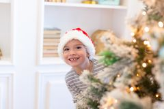 Boy in santa looks out from christmas tree. Christmas decoration. New Year and Christmas concept. Magic time. stock images