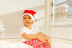 Boy in Santa`s costume dreaming sitting on his bed Royalty Free Stock Images