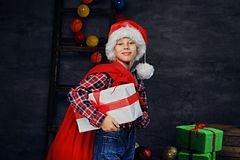 A boy in Santa`s hat holds gift box and red bag. royalty free stock photos