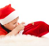 Boy in Santa's hat open christmas bag with gifts. Boy in Santa's hat open red bag with christmas gifts. Over white Royalty Free Stock Photos