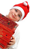 Boy in Santa's red hat carrying three presents Stock Images