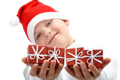 Boy in Santa's red hat holding Christmas presents Stock Photo