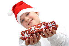 Boy in Santa's red hat holding Christmas presents Stock Photos