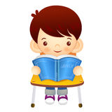 The boy sat down on the chair. Is reading a book on the desk. Ed Royalty Free Stock Photo