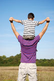 Boy sat on his fathers shoulders stock image