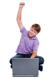 Boy sat with laptop punching the air isolated Royalty Free Stock Image