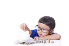 Boy saving money. Cute boy saving money in piggy bank royalty free stock photography