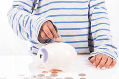 Boy saving money in piggy bank Stock Image